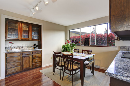 Dining area with dark brown table with fresh flowers, View of old cabinet photo