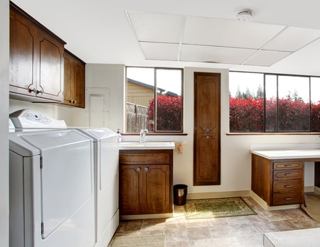 Bright white laundry room with dark brown cabinets and white appliances photo