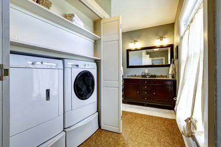 Light grey hallway in old house with brown floor built-in washer and dryer in cabinet photo