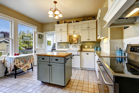 kitchen cabinets: Small kitchen interior with white wooden cabinets, tile floor and kitchen island Stock Photo