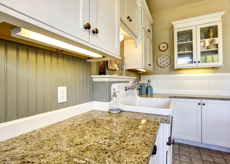 back kitchen: White old kitchen cabinets with cganite tops and plank paneled back splash trim