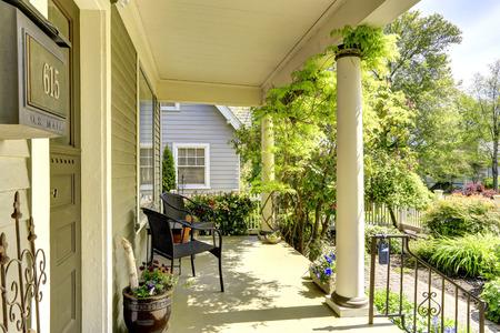 Casa exterior. Vista do jardim da frente e coluna pórtico de entrada com cadeiras