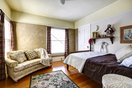 Bedroom interior with hardwood floor and rug. Furnished with high pole bed and floral sofa photo