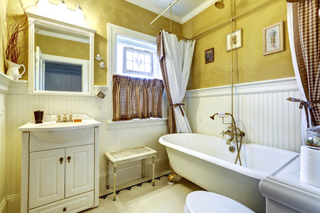 bathroom wall: Yellow old bathroom interior with white plank paneled wall trim and antique vanity and bath tub