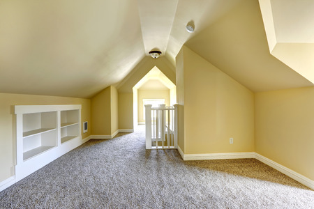 vaulted: Empty bedroom in soft ivory with soft brown carpet floor and vaulted ceiling