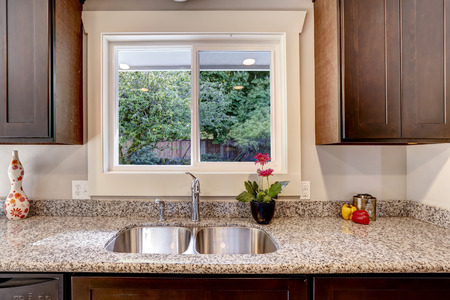 sink: Dark brown kitchen cabinet with sink and granite counter top. View of backyard through the window