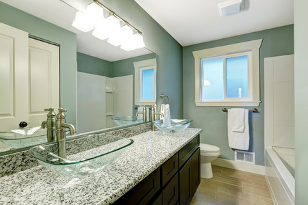 Modern bathroom interior with window. View of wooden vanity cabinet with granite counter top and glass vessel sinks Stockfoto
