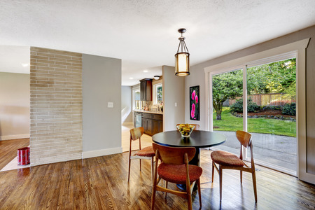 Dining area with walkout deck, hardwood floor. View of black round table with brown chairs photo