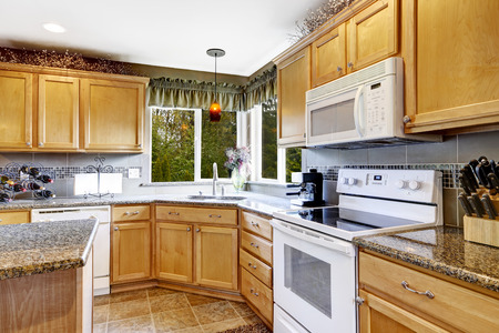 Bright kitchen room interior with tile floor, light brown storage cabinets and white appliances photo