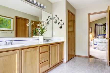Soft tones bathroom with light tone bathroom vanity cabinet and mirror