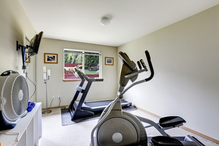 Bright gym room with exercise equipments and tv photo