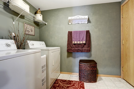 laundry room: Dark laundry room interior with white appliances and wicker basket Stock Photo