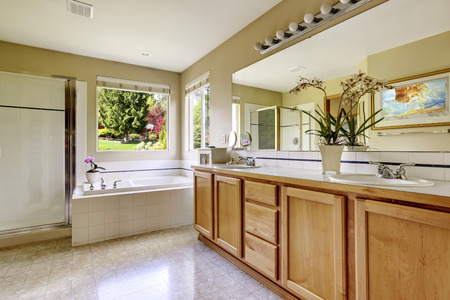 bathroom sink: Spacious bathroom interior with window. View of bathroom vanity cabinet, white bath tub and glass door shower