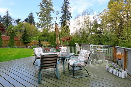Cozy wooden deck with patio table set overlooking backyard landscape photo