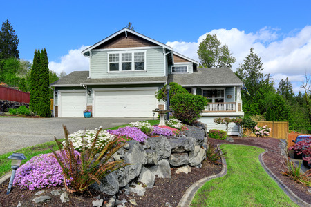 House exterior with curb appeal. View of entrance porch, garage and driveway. Beautiful front landscape