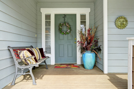 Entrance porch decorated with antique bench, big flower pot with dry branches