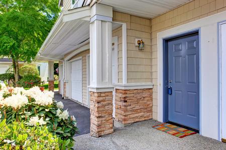Kolom entree veranda met blauwe deur en kleurrijke tapijt