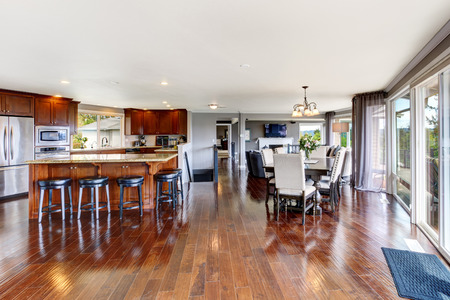 Spacious luxury kitchen room interior with kitchen island and black stools  View of dining table set photo