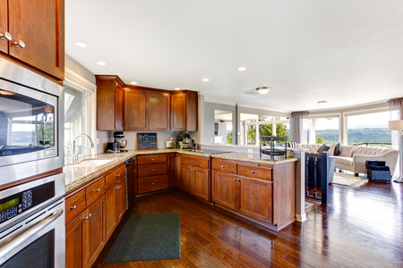 Spacious luxury kitchen room interior with brown storage combination and steel appliances