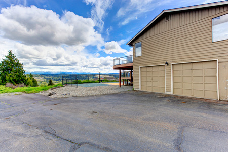 two car garage: House with two car garage and driveway. View of backyard tennis court