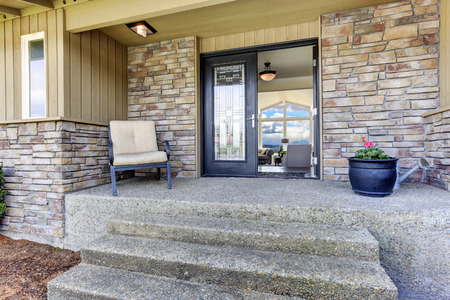 View of house entrance porch with stone wall trim and black glass door. Stock Photo