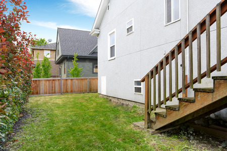 fenced: Fenced backyard with lawn and trimmed hedges. View of wooden staircase Stock Photo