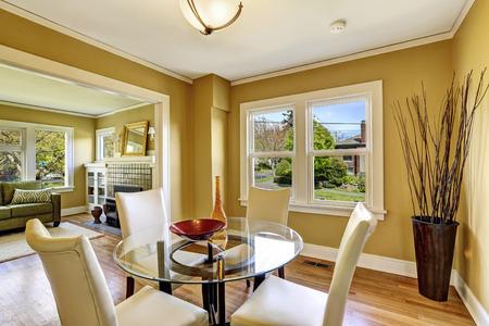 Salle à manger lumineuse avec une élégante table en verre et chaises blanches. Chambre décorée avec des branches sèches.