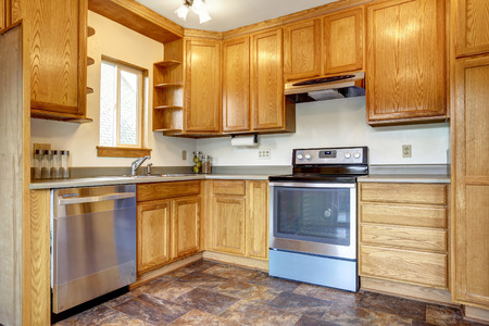 honey tone: Kitchen room interior with brown tile floor, honey tone storage combination with steel appliances Stock Photo