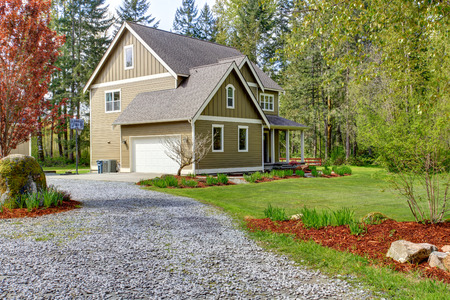Countryside house exterior with garage. View of entrance and gravel driveway 写真素材