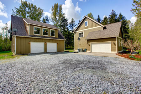 Countryside house exterior with garage. View of entrance and gravel driveway Stockfoto
