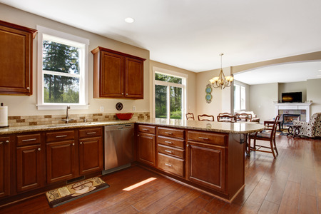 splash back: Bright kitchen room with windows. View of brown storage cabinets with tile back splash trim Stock Photo
