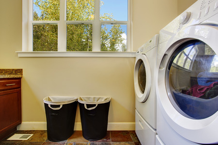 Bright ivory laundry room with white modern appliances and black baskets photo