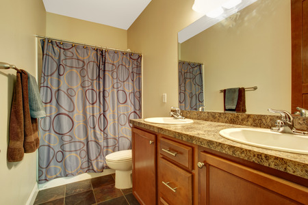 Bathroom interior in soft ivory with brown vanity cabinet and curtains