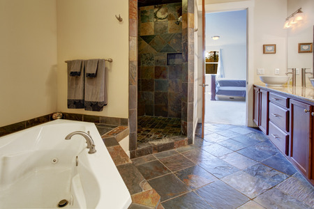 vessel sink: Bathroom interior with dark tile floor and tile shower trim. View of bathroom vanity cabinet with white vessel sink and white whirlpool tub Stock Photo