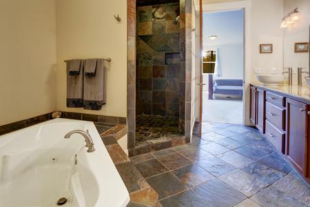 vessel sink: Cuarto de ba�o con suelo de baldosas oscuras y ducha de baldosas de corte. Vista del mueble de ba�o vanidad con blanco fregadero del recipiente y blanca ba�era de hidromasaje Foto de archivo