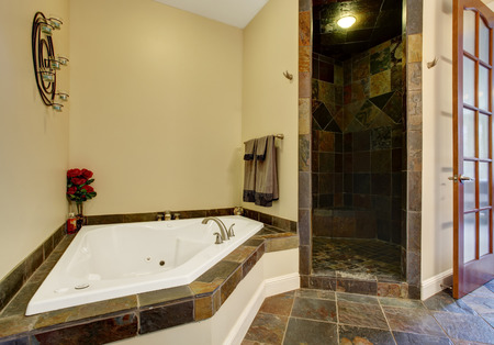 white trim: Bathroom interior with dark tile floor and tile shower trim. View of white whirlpool tub decorated with red roses