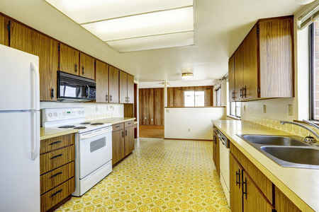 Empty kitchen room with linoleum floor, old storage cabinets and white appliances photo