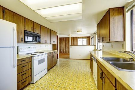 appliances: Empty kitchen room with linoleum floor, old storage cabinets and white appliances