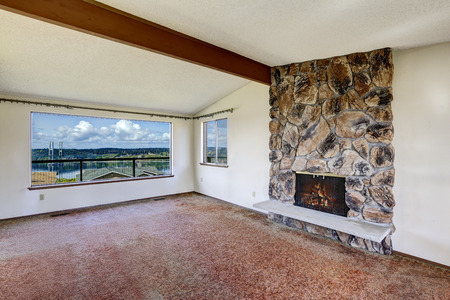 gig harbor: Bright empty living room with rocky fireplace, vaulted ceiling with beam, brown carpet floor and beautiful view of Gig Harbor bridge through the window