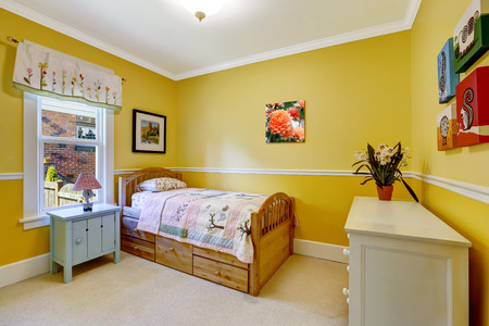 Happy kids room in bright yellow with wooden single bed and dresser photo