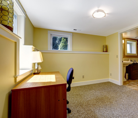 Empty office room in soft ivory with brown carpet floor with bookshelf and desk
