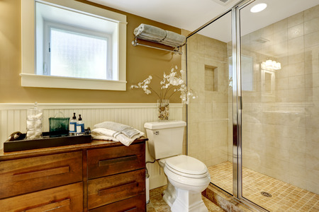 Modern bathroom interior with wooden cabinet, glass door shower and washbasin stand photo