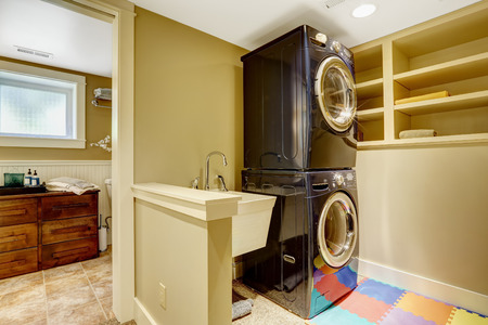 Small laundry area in bathroom. View of black modern appliances photo