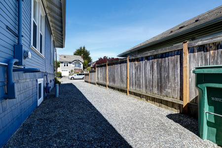 fenced in: House exterior in light blue. View of fenced backyard