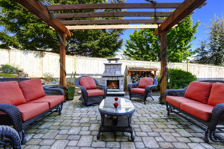 stone fireplace: Backyard cozy patio area with wicker furniture set and  brick fireplace