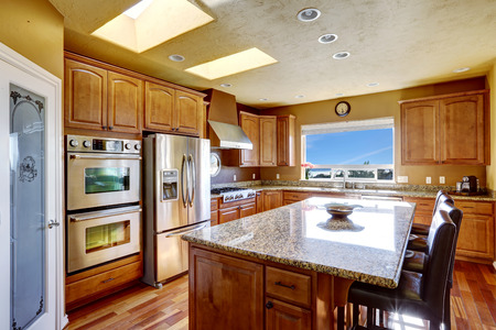 kitchen island: Luxury kitchen with SS-appliances and kitchen island with black leather chairs