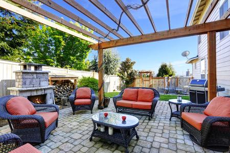 枝編み細工品の家具セットとれんが造りの暖炉と裏庭居心地の良いパティオ エリア 写真素材 - 30201448