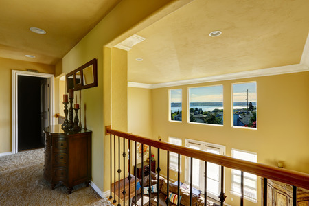 upstairs: Luxury house interior. Upstairs hallway with railings overlooking spasious living room with high ceiling and beautiful window view Stock Photo