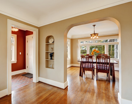 open floor plan: House interior with open floor plan. View of dining area with wooden table set and red wall hallway Stock Photo