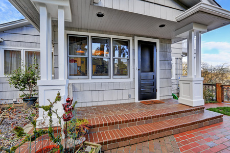 Entrance porch with brick tile floor and black door photo